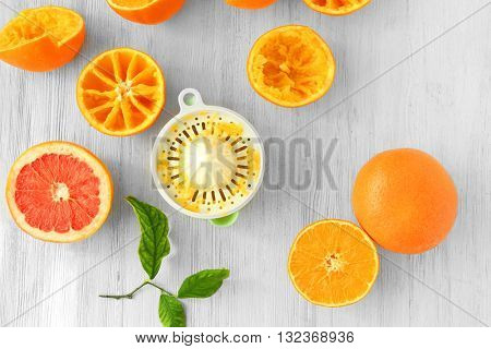 Juicy slices of oranges and juicer on white wooden table