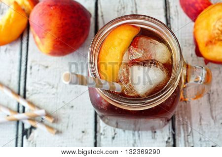 Mason Jar Glass Of Homemade Peach Iced Tea On A Rustic White Wood Background, Downward View