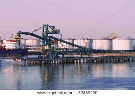 Crane And Oil Bunkers At Marina In Ventspils At Sunset