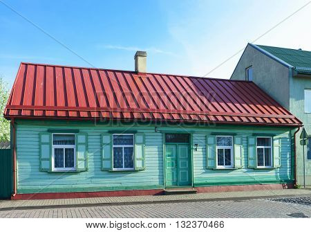 Old House Painted Green With Red Roof In Ventspils