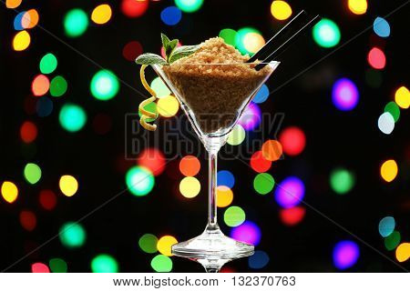 Martini glass with brown granulated sugar on dark bokeh background