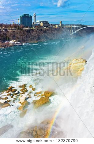 Rainbow In Niagara Falls And Rainbow Bridge Above River