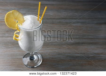 Hurricane glass with granulated sugar on wooden table