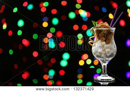 Hurricane glass with white and brown lump sugar on dark bokeh background