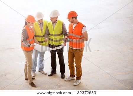 Consultation. A confident group of builders standing together, looking at plans with apprentices and talking about serious problems