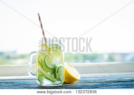 Jug With Lemon And Cucumber Infused Water On A Rustic Wooden Surface