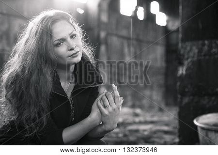 beautiful sad blonde woman in ruined building smoking sigarette, black and white concept portrait