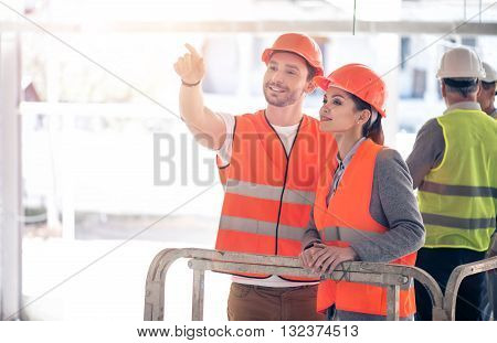 Perspectives. Smiling and cheerful businesswoman and businessman standing and talking about future plans and standing near a pair of businessmen standing together in a background