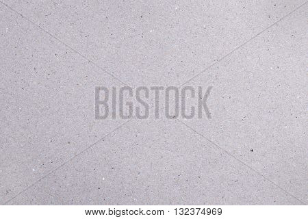 Rough gray natural cardboard background with colored dots and fibers
