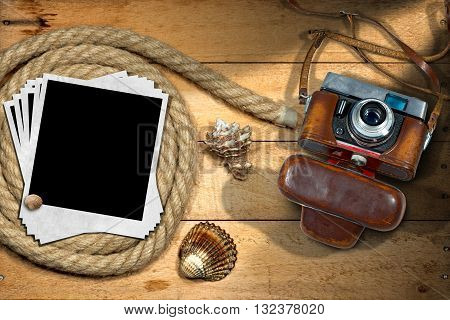 Old and vintage camera with leather case and a group of empty instant photos on a wooden background with nautical rope and seashells