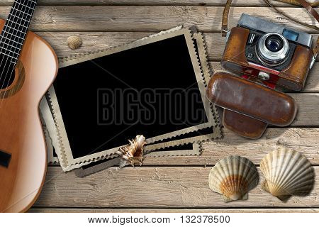 Vintage camera with leather case acoustic guitar a group of empty photos frames and seashells on a wooden boardwalk with sand