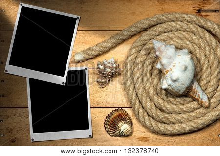 Two empty instant photos on a wooden background with nautical rope and three seashells