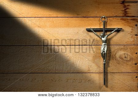 Crucifixion of Jesus Christ - symbol of Christianity on a wooden background with shadows and nails