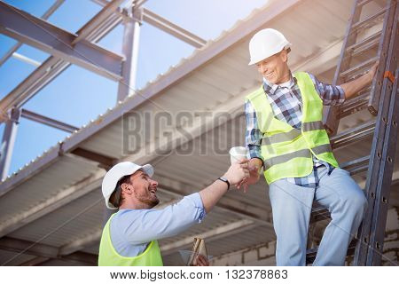 Attentive colleague. Smiling worker giving a cup of strong coffee another cheerful worker, which being on stripes while construction works