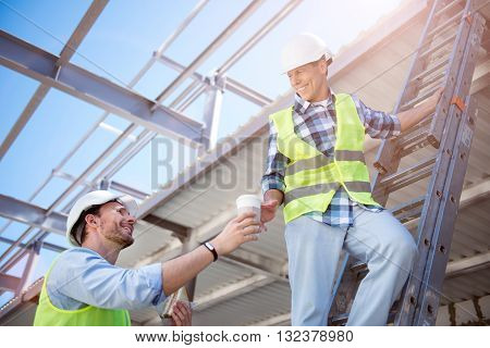 Friendly atmosphere.  Delighted and content worker giving a cup of strong coffee for another smiling worker, which being on stripes while construction