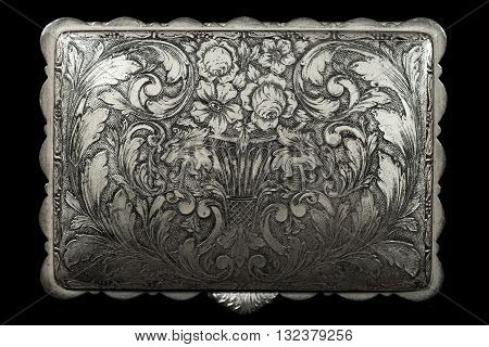 Detail of the lid of a silver box with floral vintage decoration. Isolated on a black background