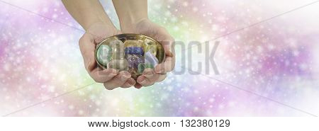 Crystal healing therapist website header - female crystal healer holding and offering brass dish with selection of healing crystals on pastel rainbow colored sparkling wide background with copy space
