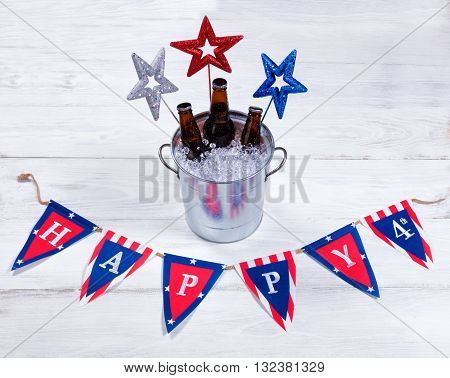 Colorful stars banner and a bucket of ice with bottled beer on rustic white wood. Fourth of July holiday concept for United States of America.
