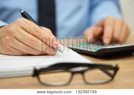 closeup of businessman reviewing financial document and calculating costs