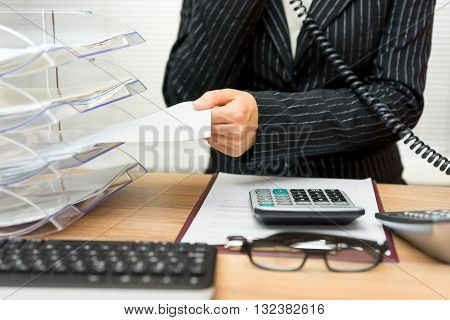 busy secretary with phone call and folders with files