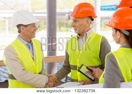Shaking hands. Cheerful and smiling engineers standing together and handshaking with construction works in a background