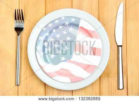 Plate with knife and fork, on wooden background. American cuisine food concept