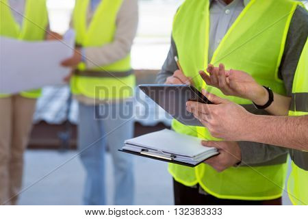 Giving a report. A pair of engineers standing together and writing down building conceptions while using a digital tablet with another pair of engineers in a background
