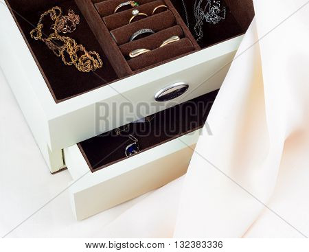 jewelry box with jewelry on silk textile background