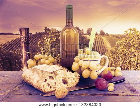 bread grapes and a bottle of wine over wooden boards on vineyard background. vintage color filtered look