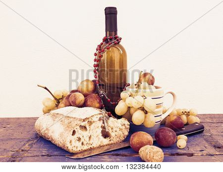 bread and grapes on white wall background