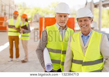 Happy to cooperate together. Content and positive pair of architects standing together and looking at a camera while holding a construction plan with a pair of another architects in a background