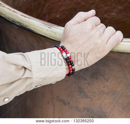 Red and black color bracelet on man's wrist
