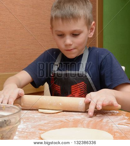 Young boy  rolling dough with a large wooden rolling pin as he prepares the cakes