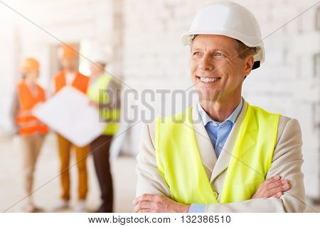 Future perspectives. Happy and wistful man in a hardhat smiling and dreaming about future with his subordinates, which holding construction plans and standing in a background