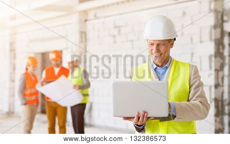Working moment. Cheerful and glad architect in a hardhat smiling and using a laptop with his colleagues, which holding a construction plan and standing in a background