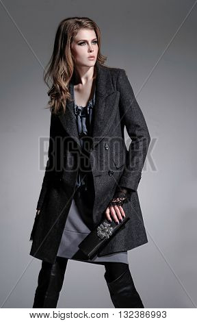 fashion model holding little purse posing on gray background