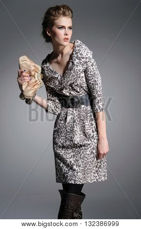 fashion model holding little purse posing on a gray background