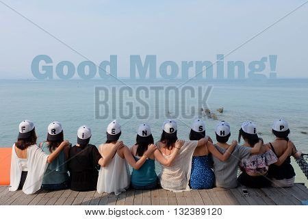 women friend group sit make arm hug hold around their friend's shoulder on wooden pier. They wear same design caps with FRIENDSHIP alphabets on each one.  looking at Good Morning! word on blue sea sky.