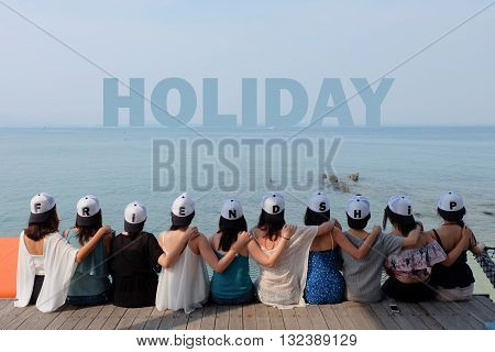 women friend group sit make arm hug hold around their friend's shoulder on wooden pier. They wear same design caps with FRIENDSHIP alphabets on each one.  looking at HOLIDAY word on blue sea sky.
