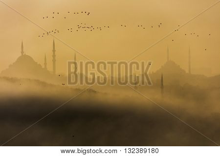 Silhouette of mosques at historical peninsula in Istanbul Turkey. Silhouette of Hagia Sophia and Sultan Ahmed Mosques in the mist. The place called historical peninsula. It's a sunset time.