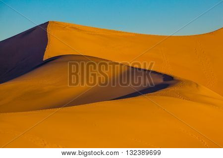The soft curves of orange sand dunes. Hot and windy morning in the desert. Hot autumn in Death Valley, California