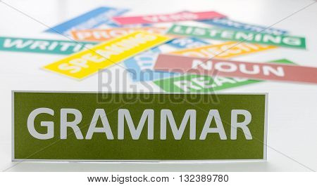 green grammar card on white table in front of colourful english cards