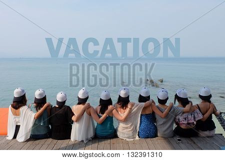 women friend group sit make arm hug hold around their friend's shoulder on wooden pier. They wear same design white and black color caps. looking at VACATION word on blue sea sky.