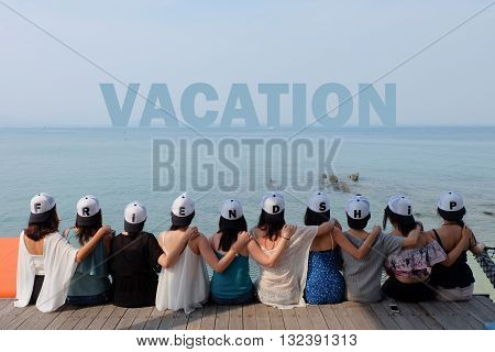 women friend group sit make arm hug hold around their friend's shoulder on wooden pier. They wear same design caps with FRIENDSHIP alphabets on each one.  looking at VACATION word on blue sea sky.
