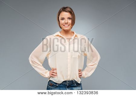 Young cute girl standing with her hands on hips isolated on the grey background