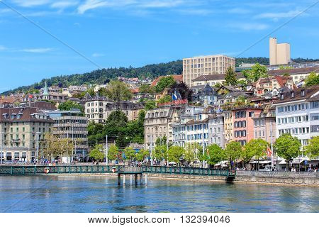 Zurich, Switzerland - 25 May, 2016: Muehlesteg footbridge over the Limmat river, people and buildings on the Limmatquai quay and Central square. Zurich is the largest city in Switzerland and the capital of the Swiss canton of Zurich.