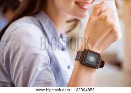 Involved in modern world. Close up of smart watch on hand of pleasant charming woman drinking coffee