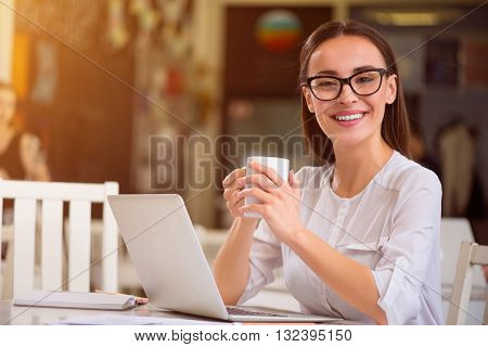 In a elated mood. Cheerful delighted beautiful smiling woman sitting at the table  and drinking coffee while expressing joy