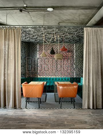 Wonderful interior in a loft style in a mexican restaurant. There is a zone decorated with metal lattices and curtains. In the zone there are green sofas, brown chairs, wooden tables and multi-colored lamps over them. On the floor there is a gray parquet