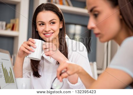 Be positive. Cheerful  beautiful smiling woman sitting at the table and drinking coffe while looking at her moody colleague